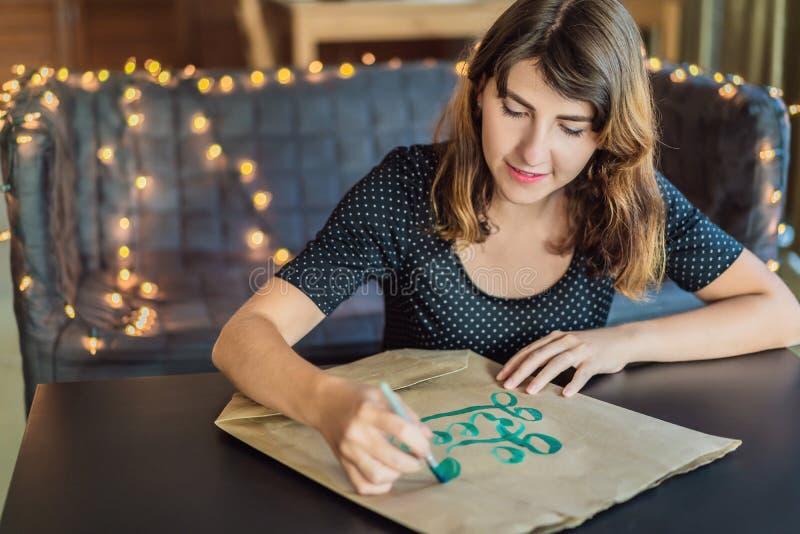 书法家年轻女人在白皮书写词组 是绿色回收 题写装饰装饰的信件 书法 库存照片