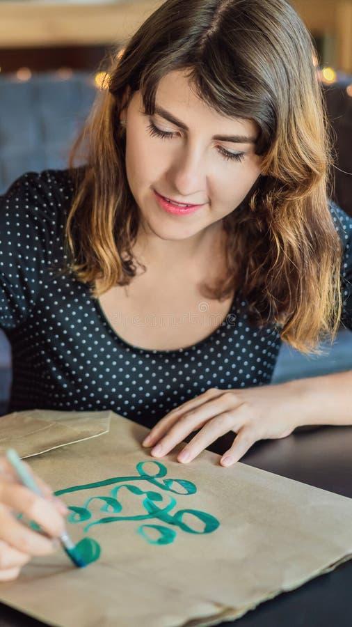 书法家年轻女人在白皮书写词组 是绿色回收 题写装饰装饰的信件 书法 免版税库存图片