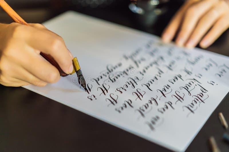 书法家手在白皮书写词组 关于题写装饰装饰的信件的爱的圣经词组 免版税库存图片
