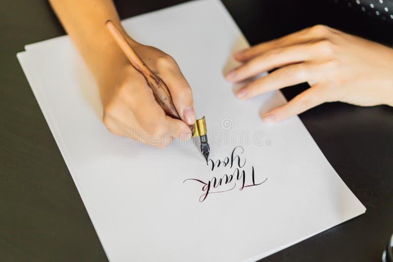 书法家手在白皮书写词组 措辞-谢谢 题写装饰装饰的信件 库存图片