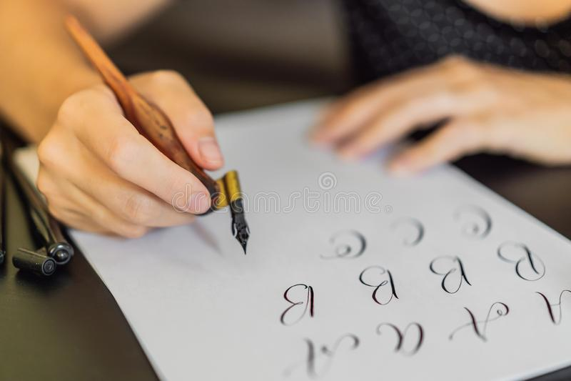 书法家手在白皮书写词组 题写装饰装饰的信件 书法,图形设计 库存图片