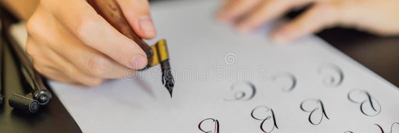 书法家手在白皮书写词组 题写装饰装饰的信件 书法,图形设计 免版税库存图片