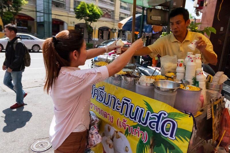 买有东方椰子味道的泰国妇女街道冰淇凌供营商在唐人街地区曼谷,泰国1月31日, 库存图片