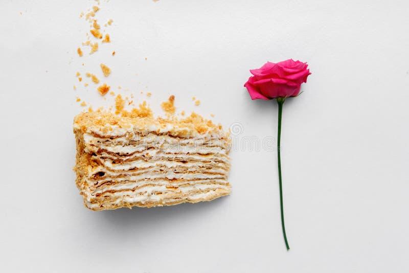 乳脂状的蛋糕片断与一朵玫瑰的在白色背景 顶视图 图库摄影
