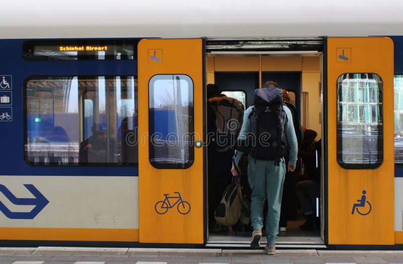 乌得勒支,荷兰,2019年2月15日:有捉住一位火车短跑选手的backback的一个旅行家在荷兰 免版税库存照片