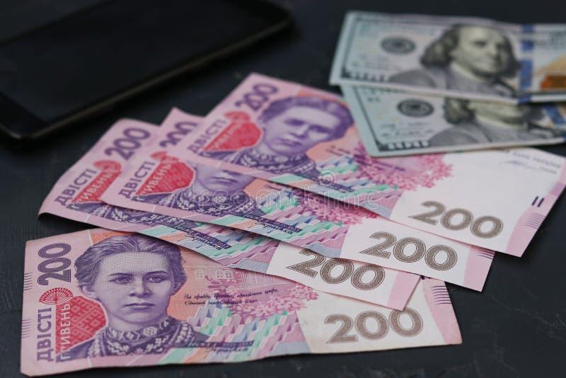 乌克兰200 hryvnia、美国一百美元和智能手机,金钱背景 库存图片