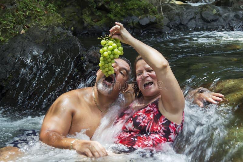 享受一天的退休的夫妇在河 库存照片
