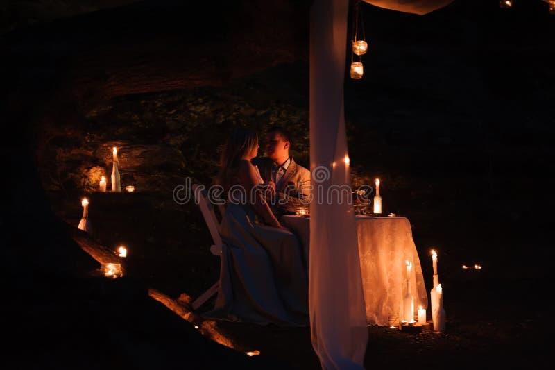 享受一顿浪漫晚餐的年轻夫妇由烛光,室外 免版税图库摄影