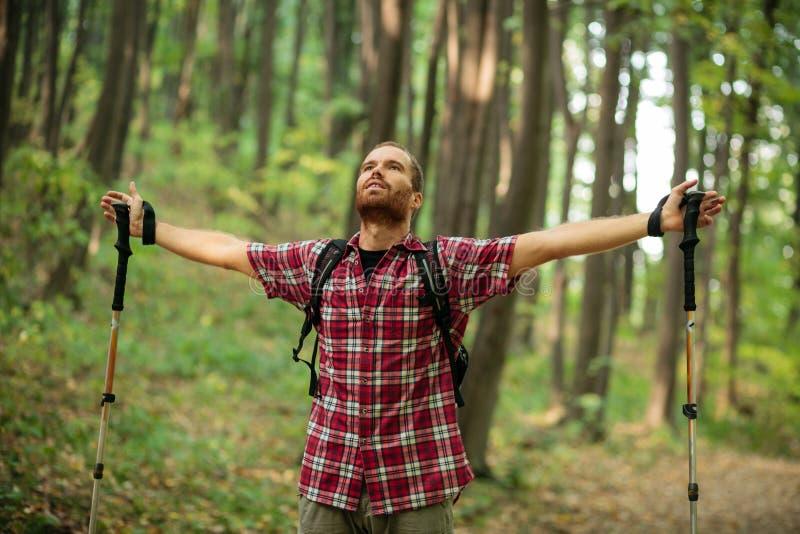 享受完善的平安的片刻的愉快的年轻人在远足期间通过被伸出的森林胳膊 库存照片