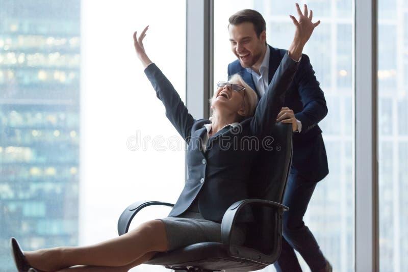 享受办公室在椅子的愉快的无忧无虑的中年女实业家活动骑马 库存图片