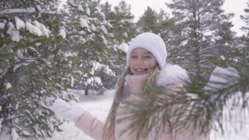享受冬天降雪的微笑的女孩在森林慢动作的多雪的天气 库存图片