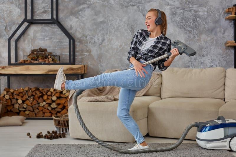 享受独奏的快乐的少妇唱歌与吸尘器,当清洗房子时 免版税库存照片