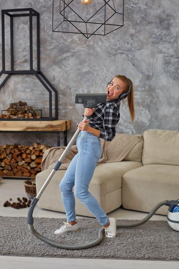 享受独奏的快乐的少妇唱歌与吸尘器,当清洗房子时 免版税图库摄影