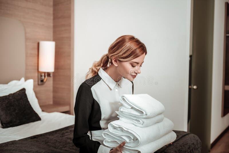 享用干净的白色毛巾的气味金发的管家 库存照片