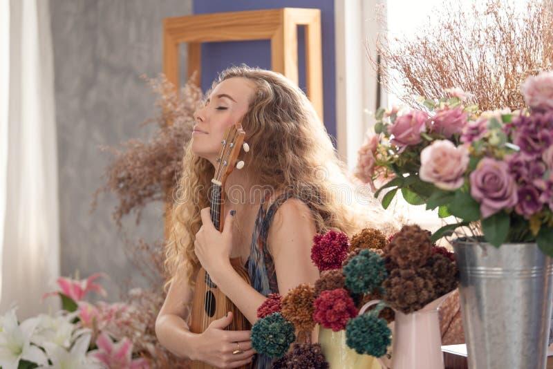 享用和放松通过演奏的微笑的妇女在音乐时间的尤克里里琴 库存图片
