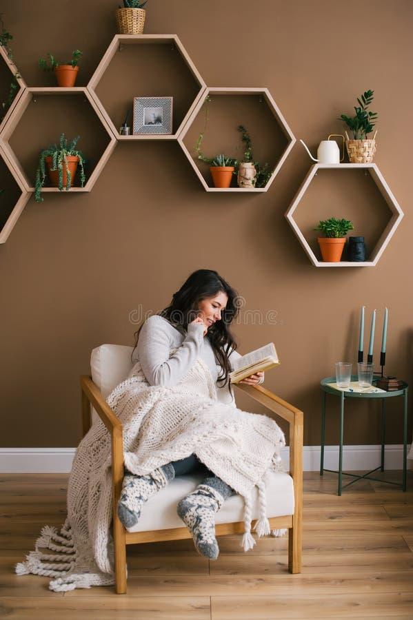 享用愉快的妇女读书坐扶手椅子在本级教室 免版税图库摄影