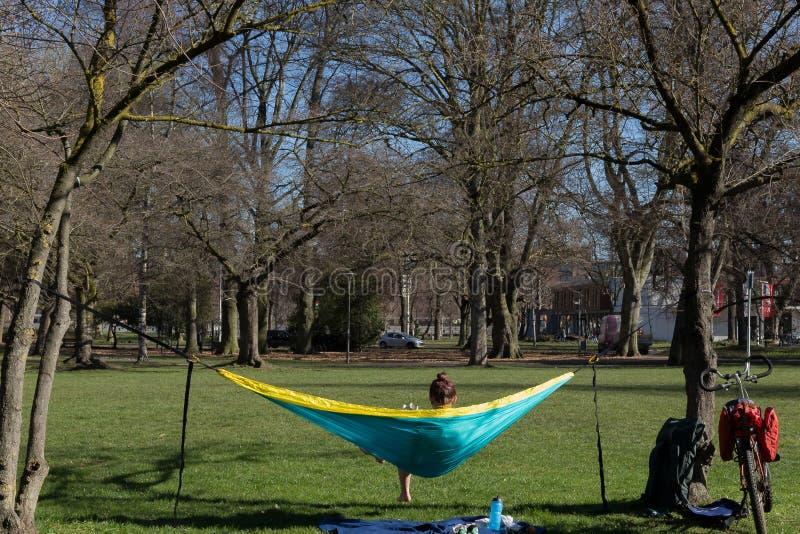 享用第一太阳和vitiamin在一个吊床的D的女孩在马斯特里赫特 免版税库存照片