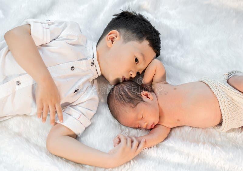 亲吻他的在床上的小男孩新生儿兄弟 免版税库存图片