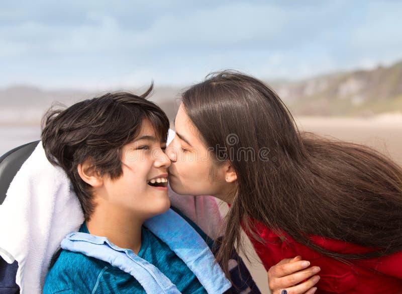 亲吻轮椅的姐姐残疾年轻男孩在海滩 库存照片