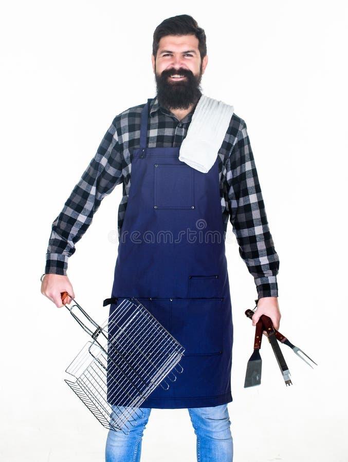 人举行炊事用具烤肉 为烤肉的工具户外 野餐和烤肉 烹调的肉技巧 库存照片