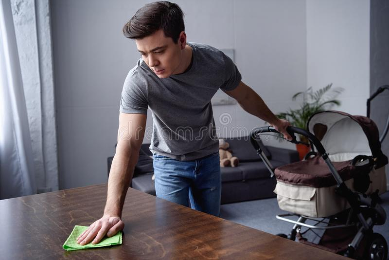 人与旧布和举行摇篮车的打扫灰尘桌用其他手 免版税库存照片