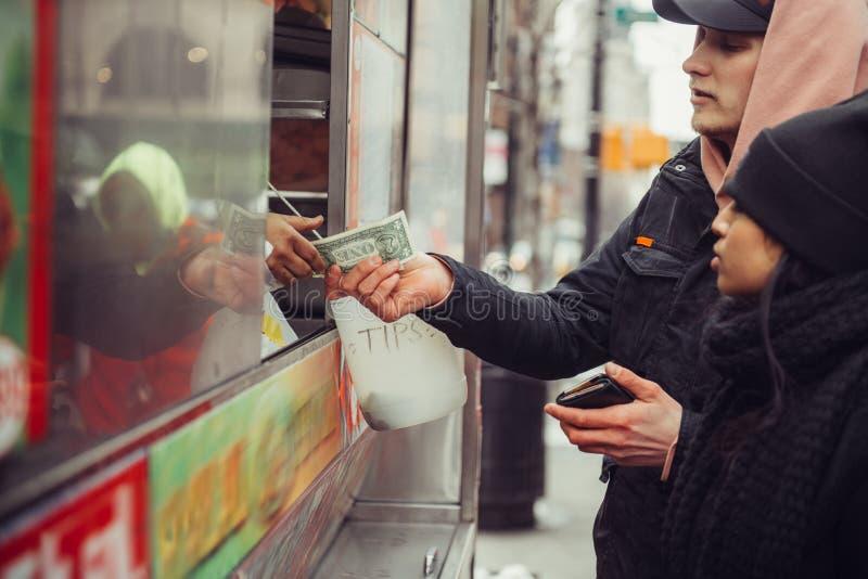 人们在纽约买街道食物并且支付现金给卖主 免版税库存照片