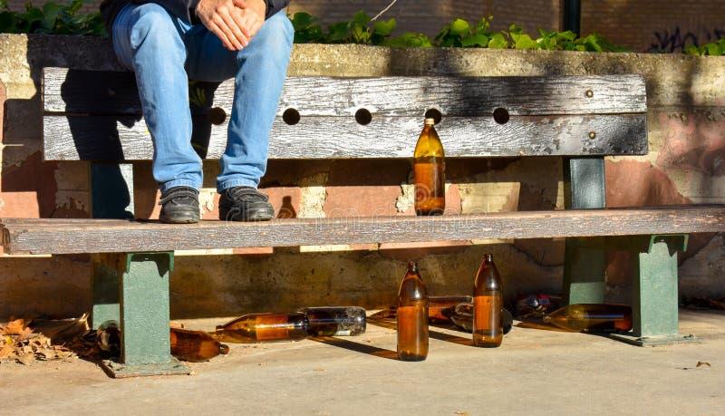 人坐与许多大橙色瓶的一条长凳啤酒由玻璃制成完全地空在公园由于某人喝了时间 图库摄影