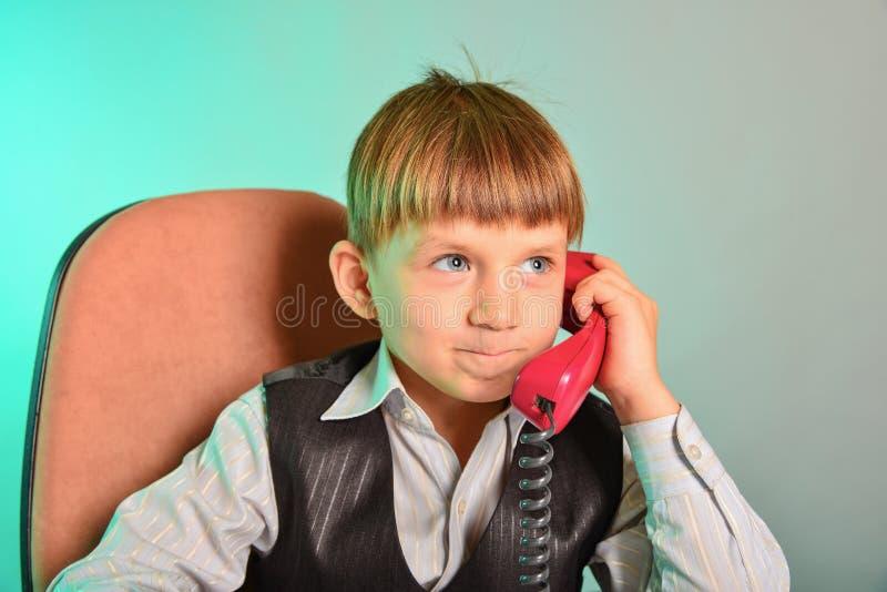 人在办公室对事态由导线电话,现代孩子的事务的概念达成协议 免版税库存照片