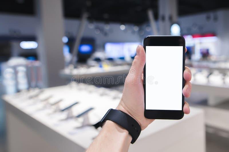 人在技术商店的背景中拿着一个智能手机 以一家模糊的商店为背景的电话 免版税库存图片