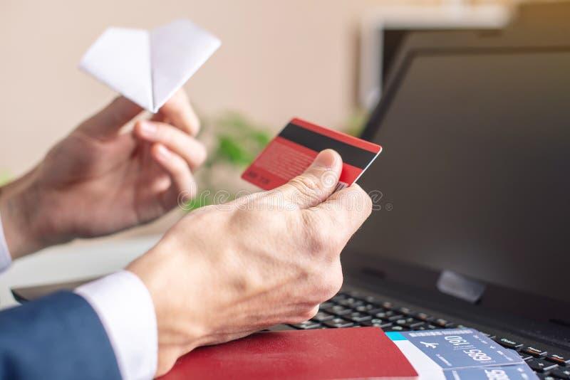 人在手中买在互联网机票的藏品借记卡使用膝上型计算机 在网上购买和预定 库存照片