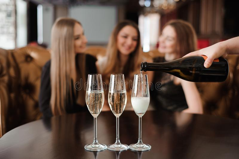 人在餐馆填装杯三美丽的年轻女人的香槟 免版税库存图片