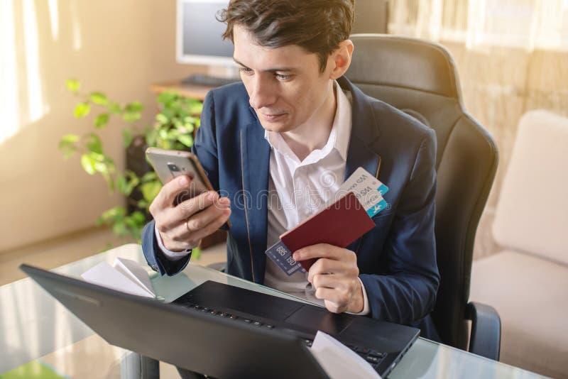 人商人藏品机票在手中和谈话在电话 在网上购买的和预定的机票 免版税库存照片