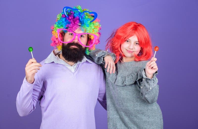 人有胡子的父亲和女孩穿戴五颜六色的假发,当吃棒棒糖糖果时 事爱的父亲为孩子做 进贡 库存照片