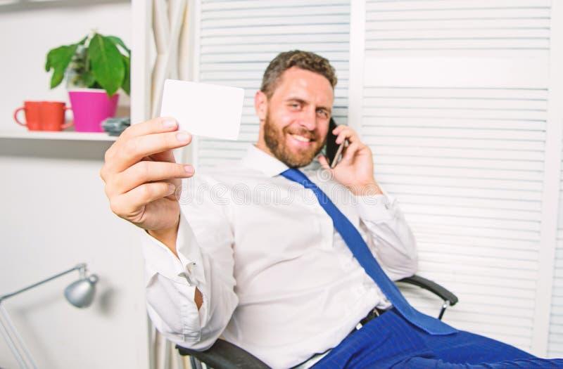人成功的商人电话交谈要求服务 商人有胡子的人坐确信办公室的感觉 人举行 免版税库存照片