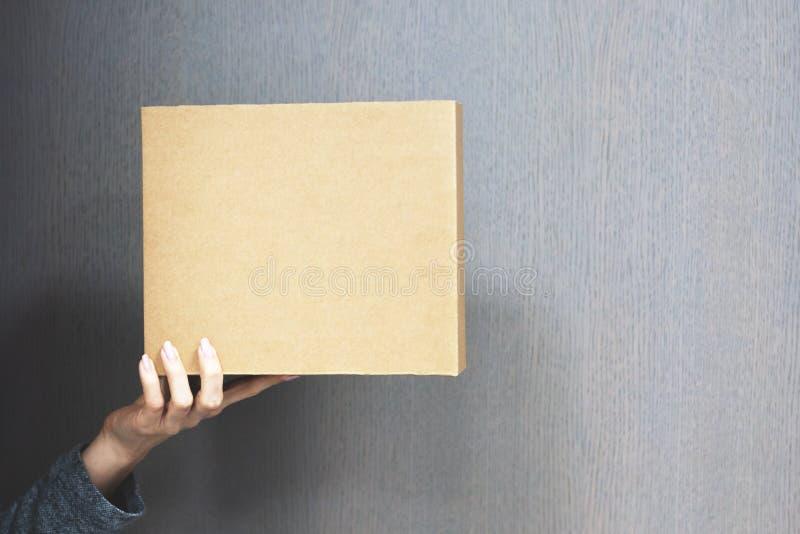 人拿着与品牌小包的包裹从互联网商店 箱子后勤学企业概念 定调子 免版税库存图片