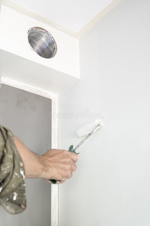 人绘画白色墙壁,有路辗的 库存照片