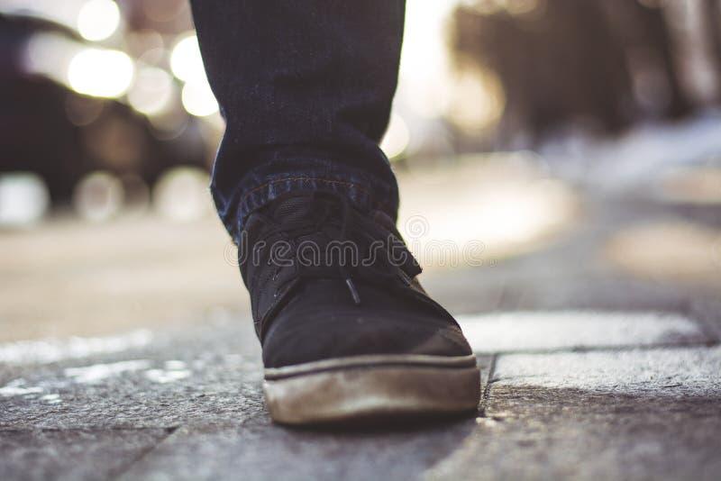 人的腿的特写镜头照片黑运动鞋的 库存照片