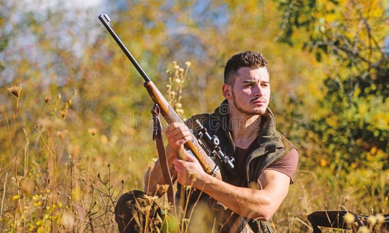 人狩猎等待动物 与步枪的猎人准备好对寻找自然背景 寻找战略或方法为 免版税库存图片