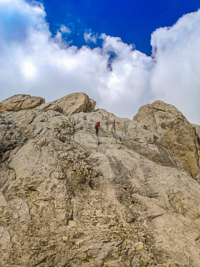 人登山人在上面攀登岩石壁架 极端休闲和冒险的概念 免版税库存照片