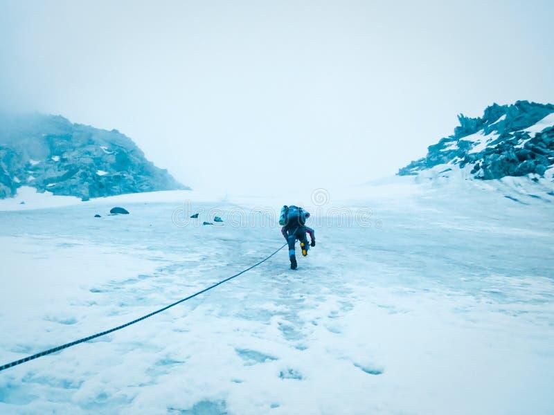人登山人攀登与一条绳索的山在冰川 极端休闲和冒险的概念 免版税库存照片