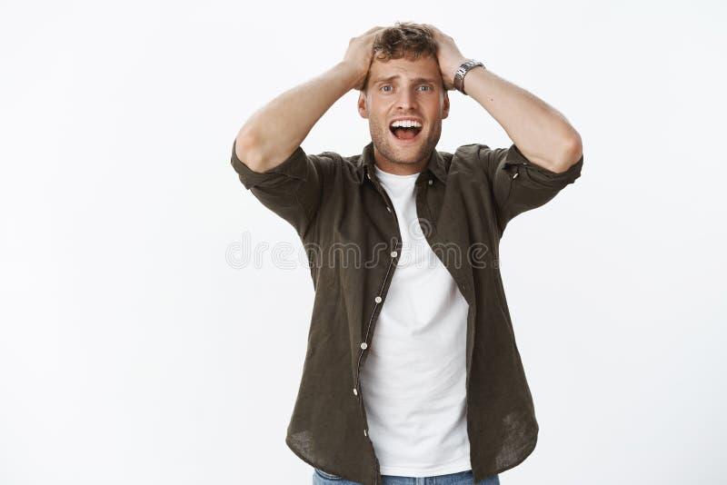 人面对失败和沮丧,感到困厄和不幸,站立排泄和弄翻在灰色背景用手 库存图片