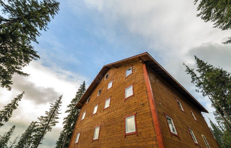 二层的木房子村庄做了委员会并且注册天空蔚蓝背景 库存图片
