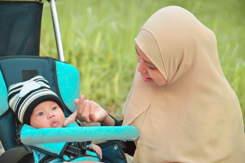 亚洲回教hijabi母亲和父亲步行通过公园有儿子的婴儿推车的,当他的照顾她的小孩时的妈妈 库存照片