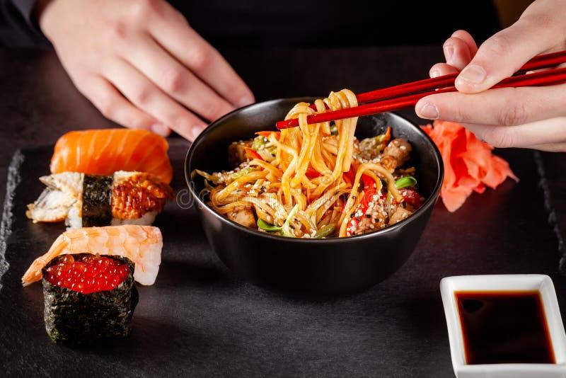 亚洲烹调的概念 女孩在她的手上拿着日本筷子并且吃着从一个黑色的盘子的中国面条 免版税库存图片