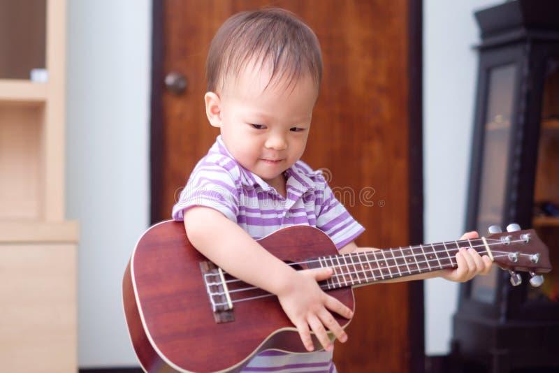 亚洲18个月/1岁男婴儿童举行&演奏夏威夷吉他或尤克里里琴 免版税库存照片