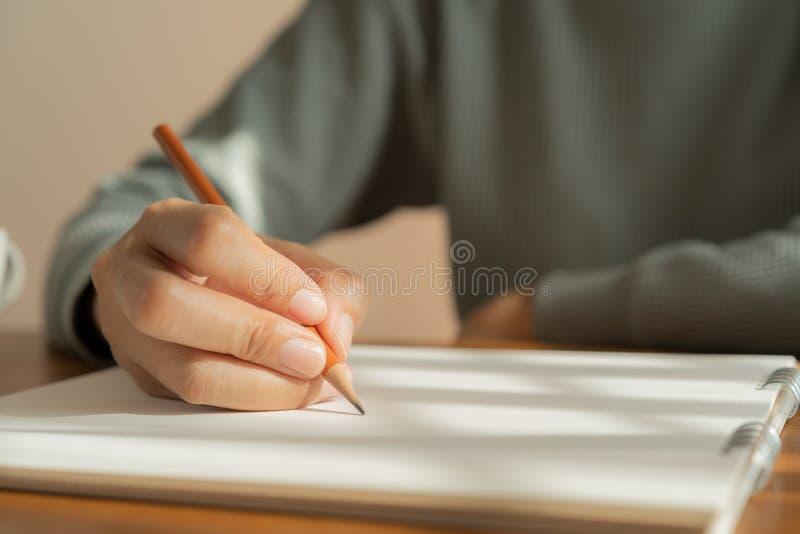 亚裔妇女的手采取关于木桌的笔记 库存图片