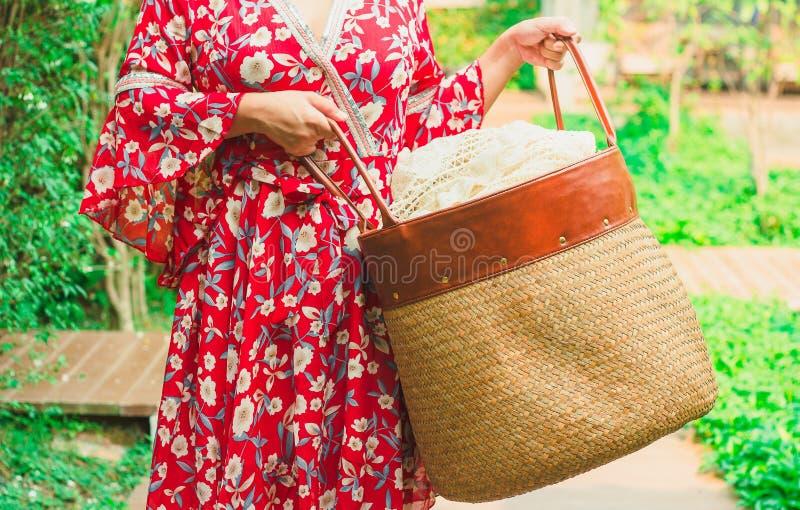 亚裔妇女运载的洗衣店布料篮子 库存照片