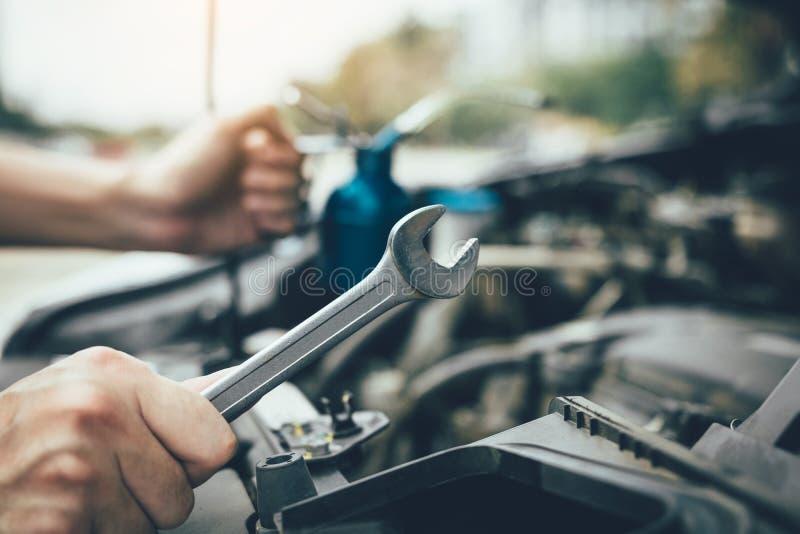亚裔汽车修理师拿着一把板钳和一个瓶诱剂油,准备好修理汽车 库存照片