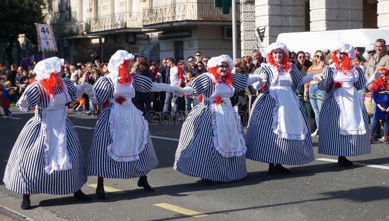 五在婴孩玩偶服装掩没的妇女,跳舞在狂欢节的街道 免版税库存照片
