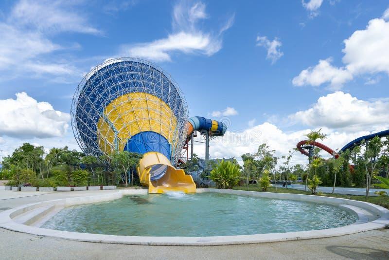 五颜六色的大锥体滑子和水池在娱乐水公园或aquapark在美好的多云和天空蔚蓝天 免版税库存照片
